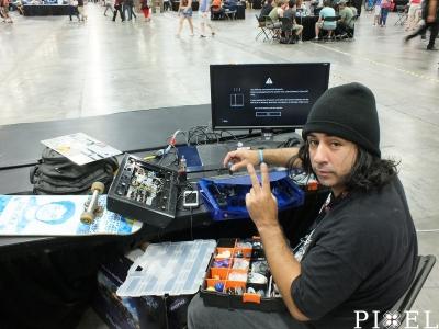 Az egyik versenyző éppen újakra cseréli a kapcsolókat a játéktermi irányítójában.