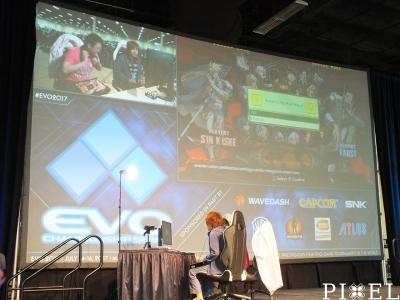 """A """"GUILTY GEAR Xrd REV 2"""" verseny legjobb meccseinek egyike látható a nagy kivetítőn, a színpadon a játékosokkal."""